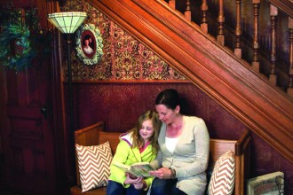 Mary Ellen Hodge (right) reads to 8-year-old daughter Adah in the formal entrance to their home in North Newton. The residence was built in 1898.