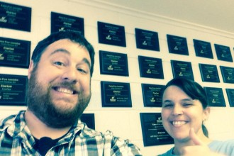 Joey and Lindsey Young take a selfie in front of the wall of awards in The Clarion office in Andale.