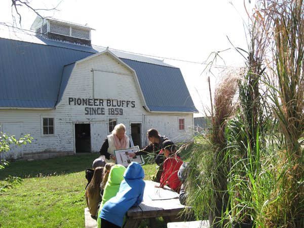 Volunteer Judith Haffner of Butler County gives a lesson to Chase County third-graders during a educational outing at Pioneer Bluffs. The historic property is open Friday-Monday and by appointment. Contributed photo