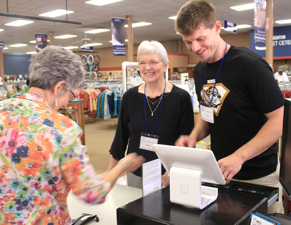 Et Cetera Shop volunteers Edna Willems, who has volunteered for 15 or 16 years, and Tyler Schroeder, who teaches business at Newton High School and started volunteering in 2015, help customer/volunteer Irma Voran make a purpose on July 15 at the store. wendy nugent/The Edge