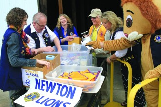 From left, Newton Lions Club members Erin McDaniel, Bob Burke, Carrie Herman, Dick McCall and Elaine Brown look through storage items in preparation for the annual pancake feed. At right is Leo the Lion. Wendy Nugent/Newton Now