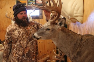 Brock Krehbiel takes a look at one of his nearly finished mounts. Krehbiel has been in taxidermy for eight years and has done it full-time for two years. Photo by Clint Harden