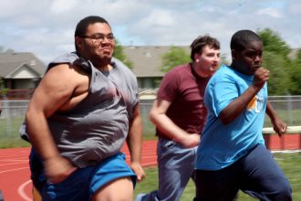 Tristan Smith (left) races Elijah Green (right) to the finish line while Brice Moser (middle) makes a push from behind on April 30 at Newton High School. Photo by Mike Mendez, Newton Now
