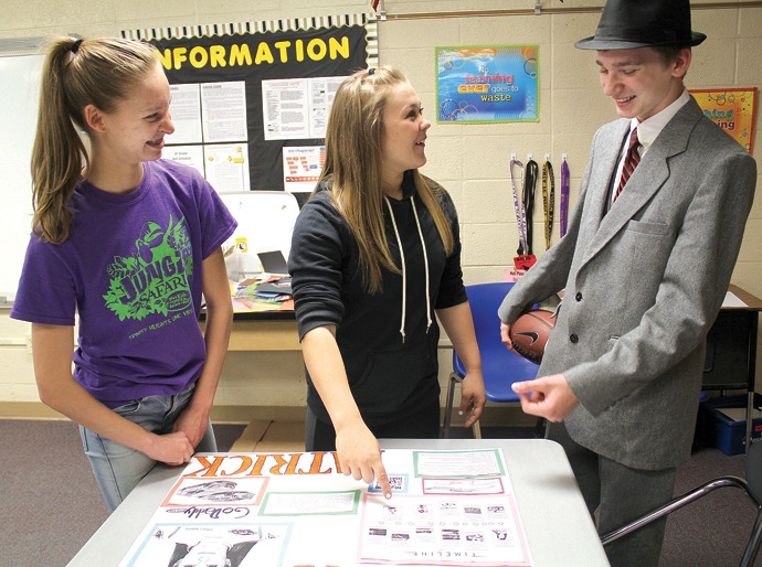From left, eighth-grade Chisholm Middle School students Jaden Anton, Reagon Moe and Josh Edson (dressed as Vince Lombardi) talk about Moe's poster for the wax museum project. Wendy Nugent/Newton Now
