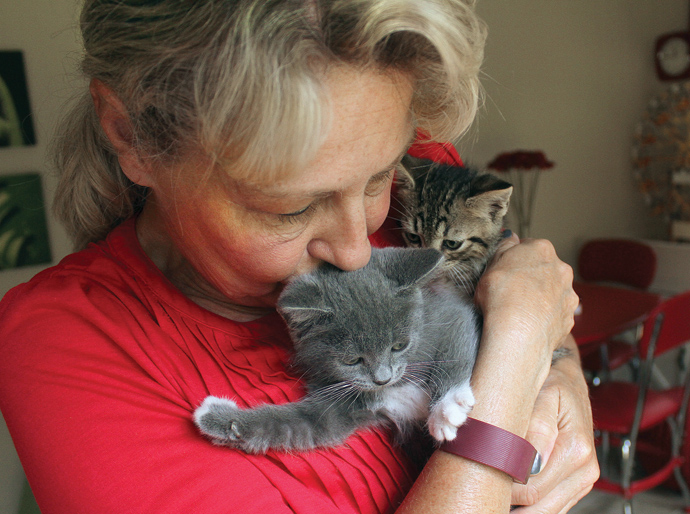 Pat Tongish nuzzles with two kittens who survived a drive from Hesston to Newton in a van engine. Wendy Nugent/Newton Now