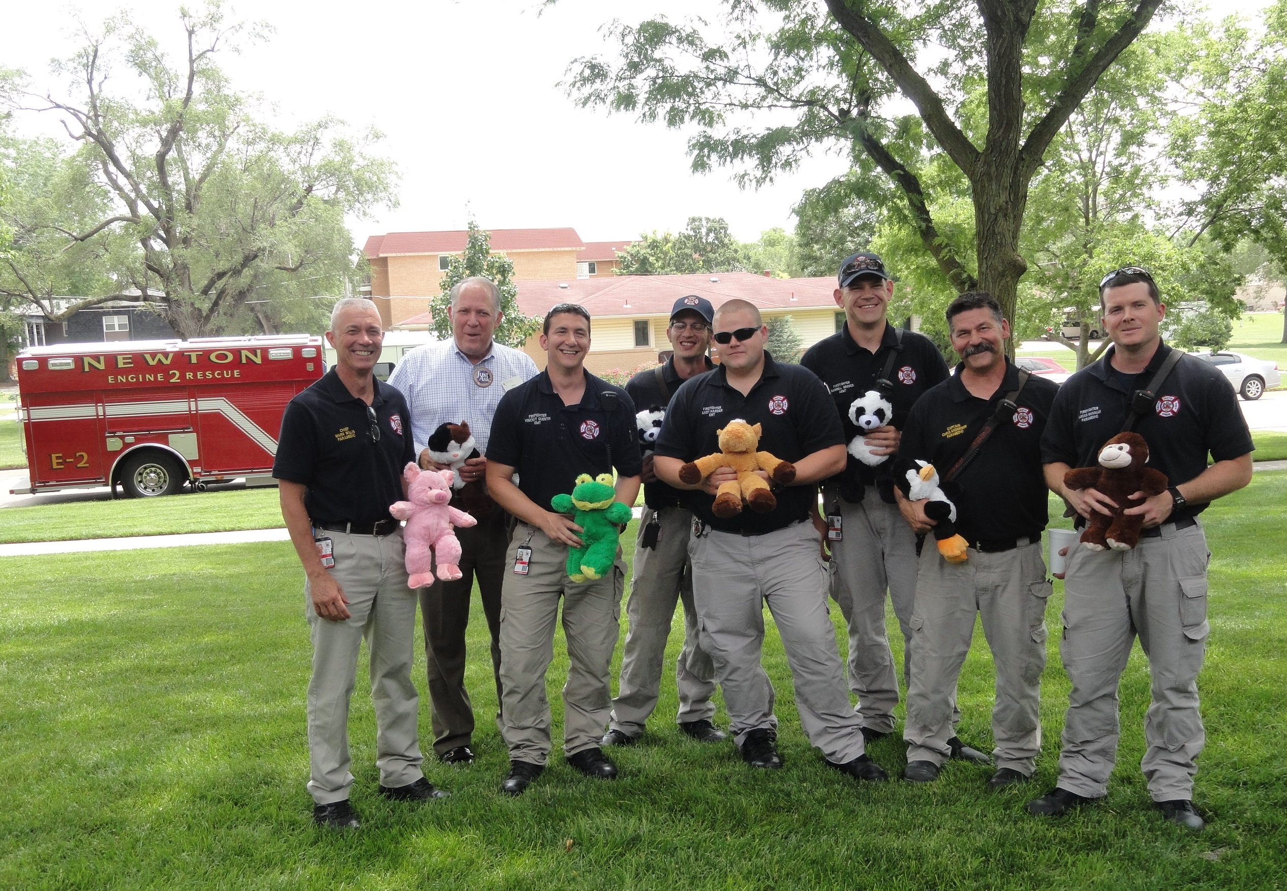 First responders hold stuffed animals made by residents of Presbyterian Manor. The animals were made to present to children when responding to crisis calls. Presbyterian Manor hosted first responders at a Flag Day ice cream social
