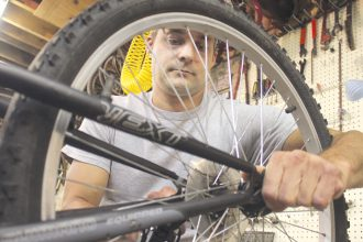Jeremy Ewy works on a bike on Monday, Aug. 22, at the Newton Et Cetera Shop. Wendy Nugent/Newton Now