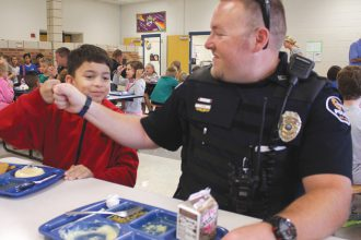 School Resource Officer Jon Adkins, right, does a fist bump with student Emilio Martindale on Thursday at South Breeze Elementary School. A number of Newton Police Department officers had lunch with the students. Wendy Nugent/Newton Now