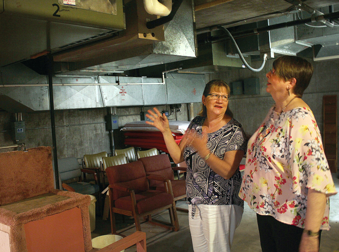 Betty Lanzrath, left, president of the Newton senior center board of directors, and Leslie Runnalls, senior center director, talk near the air handler in the basement of the senior center that sounds like an industrial sewing machine. Wendy Nugent/Newton Now