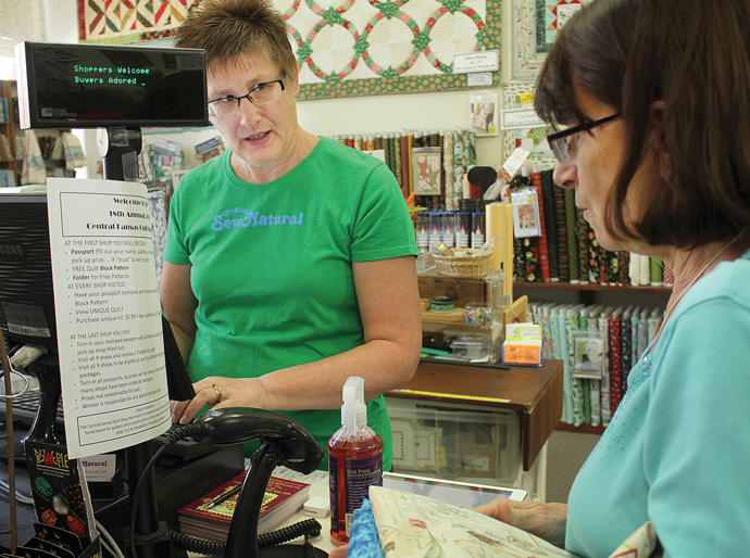 Charlotte's Sew Natural employee Rita Ullum, left, helps customer Sandy Whiting check out on Thursday during the 2016 Central Kansas Quilt Shop Hop. Wendy Nugent/Newton Now