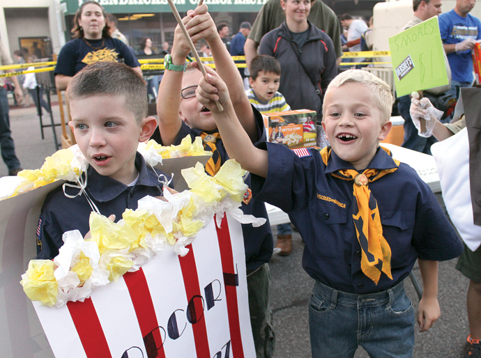 """Cub Scouts with Pack 127, from left, Tyler Hagman, Logan Hensiek and Brady Weimer with Pack 127 in Newton yell """"popcorn"""" over and over, since their group sold popcorn during Taste of Newton on Thursday night. Wendy Nugent/Newton Now"""