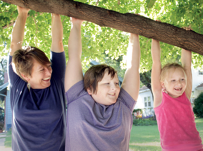 Bev Baumgartner, left, hangs out with her children, Henry and Anna Ewy, on a limb of the tree in which Baumgartner has been filming. Wendy Nugent/Newton Now