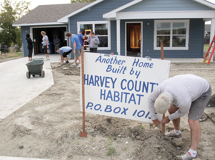 Harvey County Habitat board member Mike Schmidt, right, works on taking down the Habitat sign at the most recent home, which will be owned by Karen Schwind, while other volunteers works outside on Saturday morning. Wendy Nugent/Newton Now