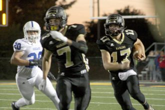 Newton quarterback Landon Moore (17) looks for a lead block from Kade Remsberg (7) in a loss to Goddard on Oct. 21 at Fischer Field. Mike Mendez/Newton Now
