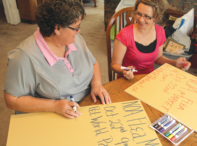 Stephanie Phelps, left, and Heather Murrow, both administrators on the Newton Online Auction Facebook site, work on posters for the upcoming Newton Online Auction Fall Flea Market. Wendy Nugent/Newton Now
