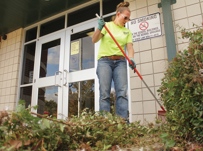On Thursday, Missy Green uses a rake to help clean up the front area of Sunset Elementary School in Newton. Wendy Nugent/Newton Now