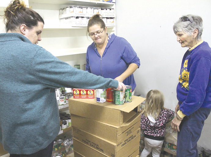 Working on stacking cans in the food pantry at First Christian Church in Newton are, from left, Allison Hammond, Erin Bales, her daughter Cierra and Shirley Grosch. Wendy Nugent/Newton Now