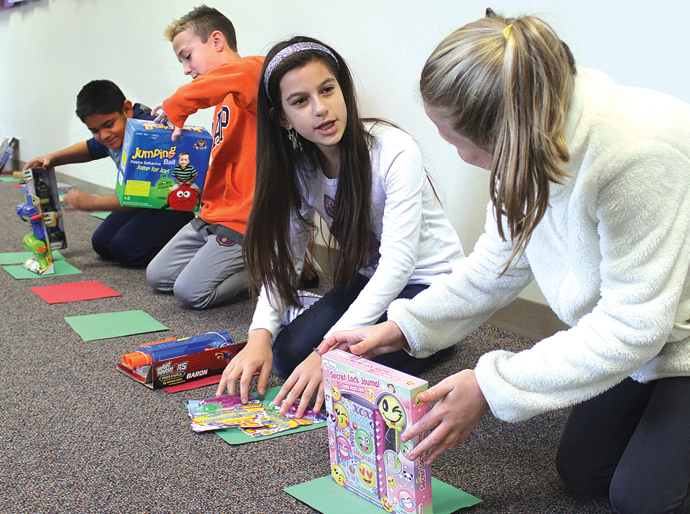 Students Offering Service (SOS) members, from left, Omar Lizcano, George Bates, Karla Correa and Ryleigh Willis put out toys for the toy drive at South Breeze Elementary School in Newton. Wendy Nugent/Newton Now