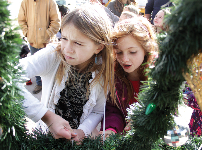 Chloe Harder, left, makes a face while attaching an ornament to the Christmas tree in downtown Walton. At right is Maisie Brubacher. Wendy Nugent/Newton Now