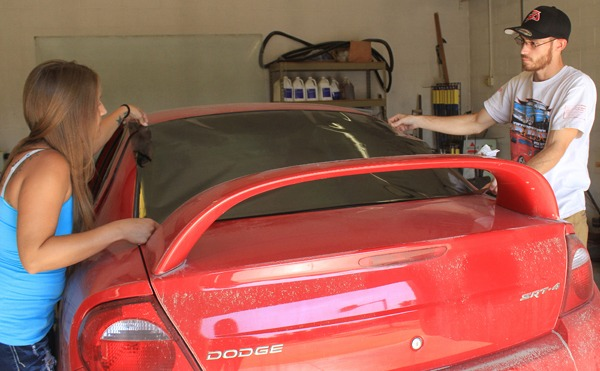 Viktoria Bichet and Jesse Boucher work on tinting a vehicle window this past fall at ASAP AutoWorks in Newton. Both are members of Newton Young Professionals.