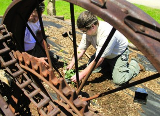 Kass Miller, right, director of Harvey County Parks, and Jerry Howe, park ranger, work on a xeriscaping project May 18 at East Park. Framing them is a wheel from an old piece of farm machinery that is part of the decorations.