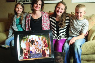 Michelle Ruebke, second from left, sits in the family room with three of her children, from left, Meghan, 10; Grace, 14; and Michael, 10. The photo in the foreground shows the entire family with Ruebke children, their spouses, grandchildren and a great-grandmother. Five of the Ruebke children still reside at home.